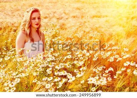 Blond beautiful girl at chamomile field. Pretty looking young woman at meadow of daisy flowers and summer green nature. Harmony concept  - stock photo