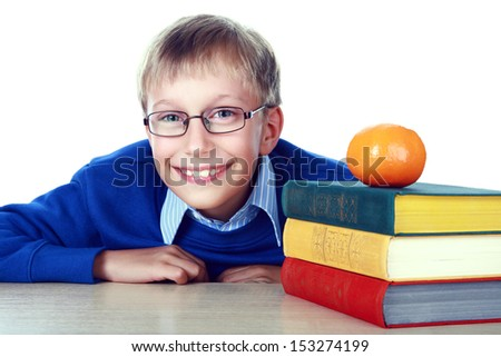 Blond beautiful schoolboy sitting at a table with a stack of colorful books laughing (isolated on white background) - stock photo