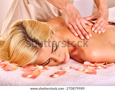 Blond beautiful woman getting massage. Hands on shoulder - stock photo