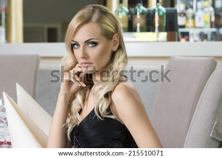 blond beautiful woman sitting at restaurant . very elegant , waiting for someone . looking in camera - stock photo