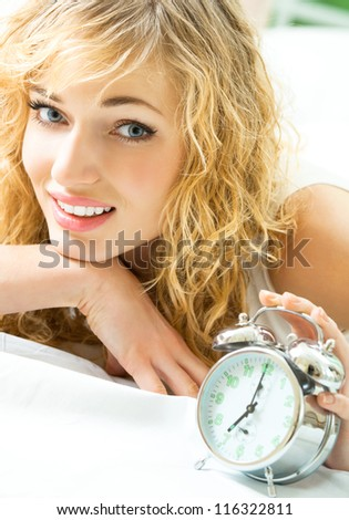 Blond beautiful woman with alarmclock on the bed - stock photo
