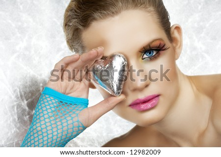 Blond beautiful woman with blue eyes and fashion make-up holding a silver heart, wearing blue fingerless gloves. Not isolated - stock photo