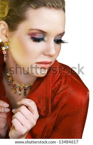 Blond beautiful woman with long fashion lashes and pink lips in red jacket and colourful necklace and earrings - stock photo