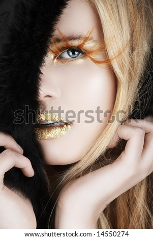 Blond beautiful woman with long hair, false feather eyelashes, fur trim and gold leaf on her lips - stock photo