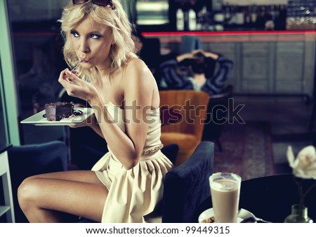 Blond beauty eating a cake