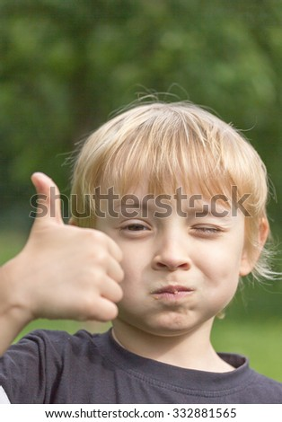 Blond boy ate cake and still has crumbs a on his face. Thumbs up is showing that he liked. - stock photo