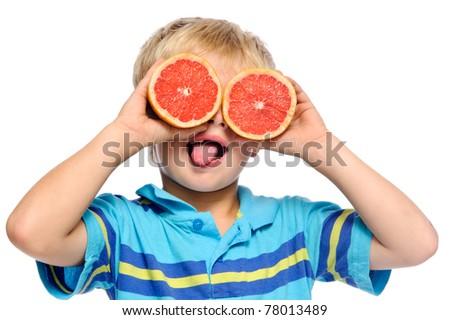 Blond boy covers eyes with ruby grapefruit and sticks his tongue out - stock photo