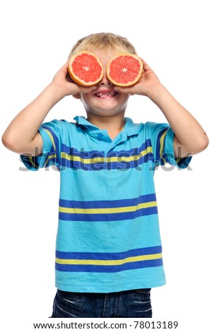 Blond boy covers eyes with ruby grapefruit; healthy living concept - stock photo