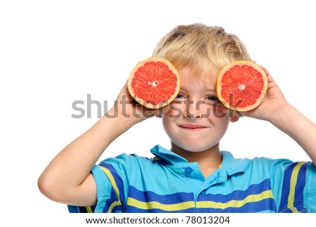 Blond boy covers face with ruby grapefruit; healthy living concept