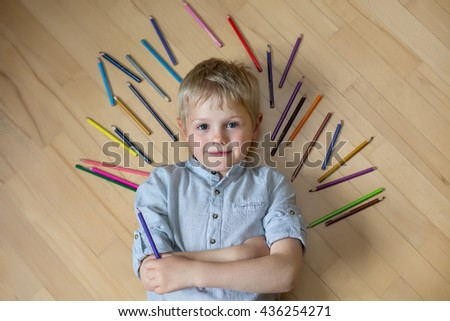 blond boy in a shirt lying on the floor next to the pencil - stock photo