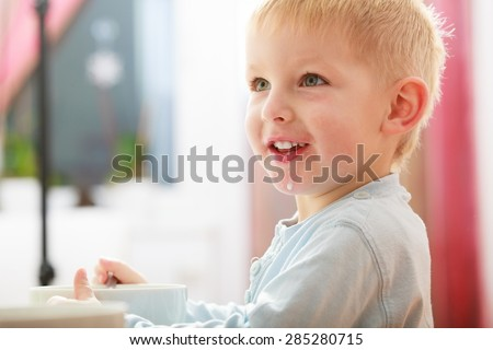 Blond boy kid child eating corn flakes breakfast morning meal at the table. Home. - stock photo