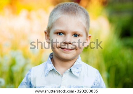 blond boy of five in the field of dandelions in the sunset light is beautiful and smiling - stock photo