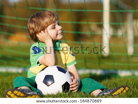 Blond boy of 4 playing soccer with football on football field, outdoors. - stock photo