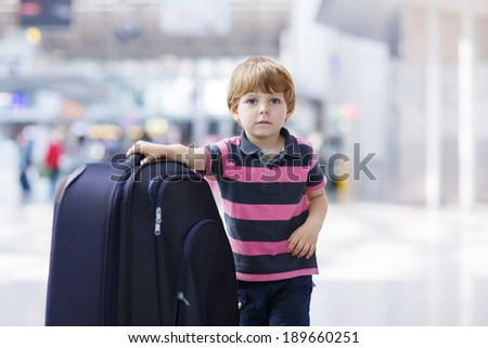 Blond boy of 4 years with huge suitcase at the international airport, indoors and waiting for going on vacations. - stock photo