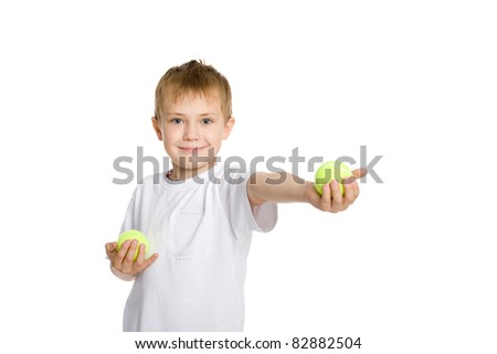 Blond boy playing in the tennis balls. - stock photo