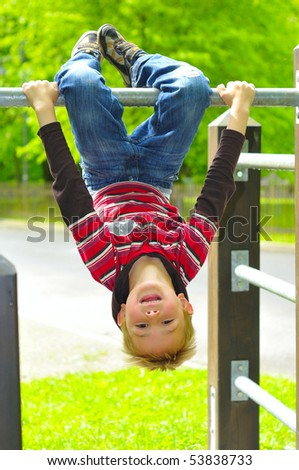 Blond boy playing on the jungle gym. - stock photo