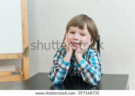 Blond boy sitting at the table at home and learns. The idea of school, school, home education and developmental activities. - stock photo