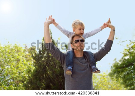 Blond boy sitting on fathers shoulder outdoors. Coloring and processing photos in vintage style with soft selective focus - stock photo