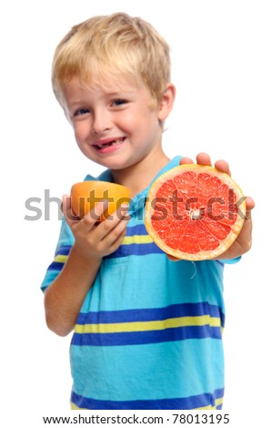 Blond boy with a fresh ruby grapefruit; healthy living concept selective focus on fruit