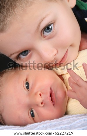 Blond boy with his newborn baby brother - stock photo