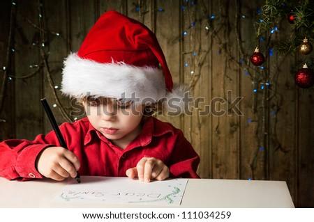 Blond boy writes a letter to Santa - stock photo