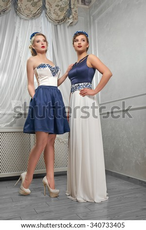 Blond, brunette women in red and peach dresses, hands on hips, on hills, on white background in the room. - stock photo