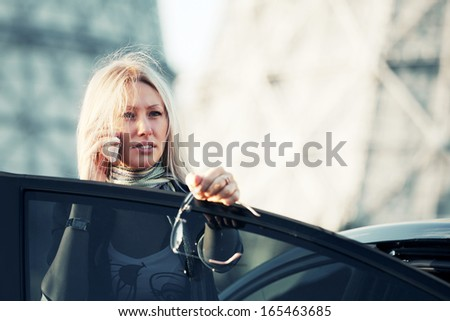 Blond business woman calling on the cell phone at the car - stock photo