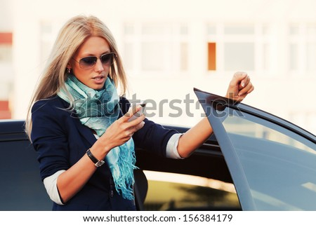 Blond business woman looking at a mobile phone - stock photo