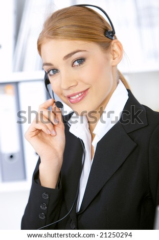 Blond business woman working in office, wearing headset