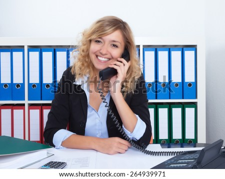 Blond businesswoman at office speaking with client at phone - stock photo