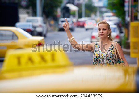 blond businesswoman calling yellow taxi with arm raised in street. Tourism and business travel  - stock photo