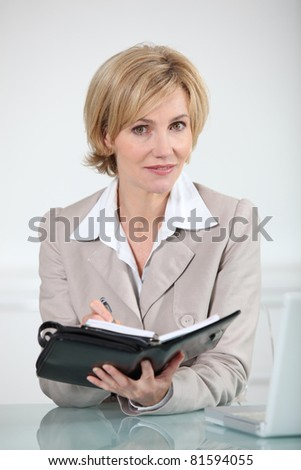 Blond businesswoman sat at desk with diary - stock photo