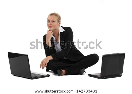 Blond businesswoman sat on the floor with two laptops - stock photo