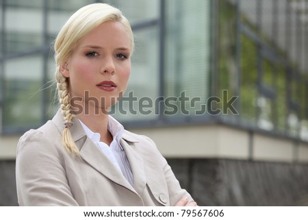 Blond businesswoman stood outside building - stock photo