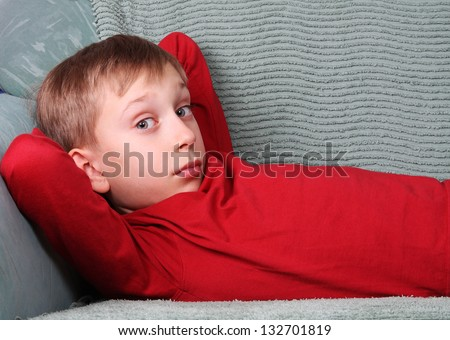 Blond Caucasian boy in red lying on green sofa relaxing looking into the camera offended - stock photo