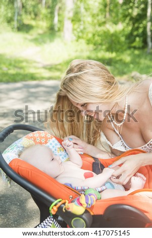 blond caucasian mother hold hands her naked baby in stroller outdoor at summer park. Empty space for inscription - stock photo