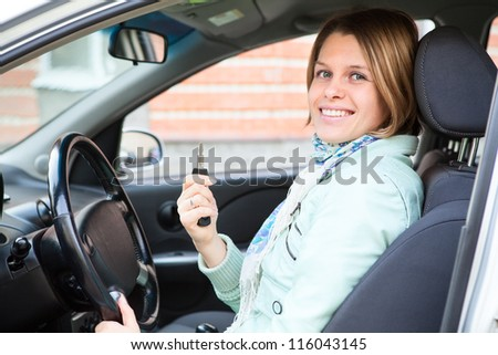 Blond Caucasian woman showing car key in vehicle