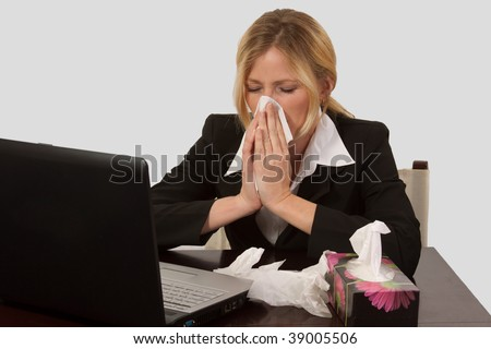 Blond caucasian woman wearing business attire sitting in front of laptop computer with a box of tissues blowing her nose - stock photo