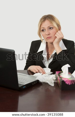 Blond caucasian woman wearing business attire sitting in front of laptop computer with a box of tissues - stock photo