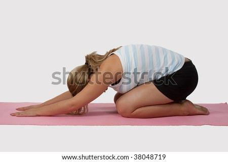 Blond caucasian woman wearing workout attire on knees bowing down on a pink mat over white