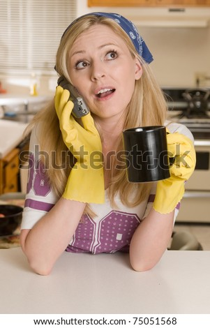 Blond caucasian woman wearing yellow cleaning gloves and hair scarf holding a cup of coffee talking on phone while leaning on a kitchen counter