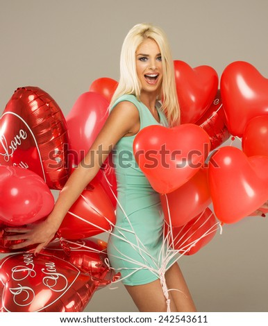 Blond cheerful woman with red balloons heart - stock photo