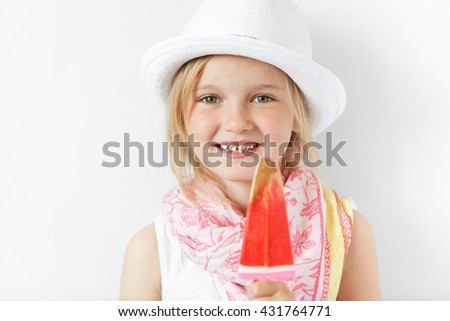 Blond child with contended smile and yummy lollipop looking forward with joy and natural simplicity. Nothing could be better than summertime free atmosphere, sweets, sunshine and happy kid. - stock photo