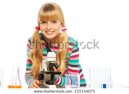 Blond clever teen schoolgirl in the laboratory with microsope and teset equipment - stock photo