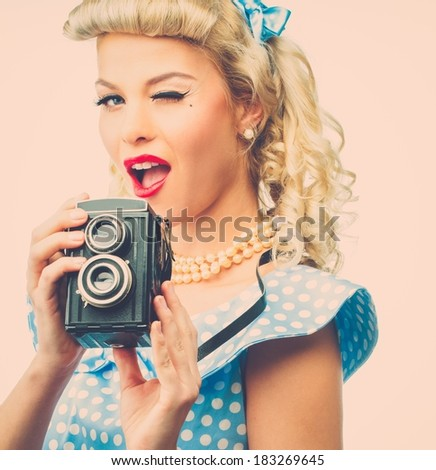 Blond coquette pin up style young woman in blue dress with vintage camera  - stock photo