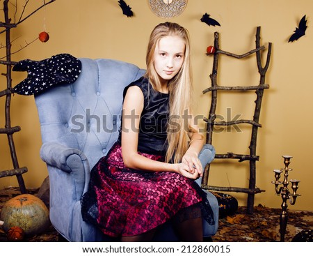 blond cute girl in halloween interior with pumpkin, cute teen - stock photo