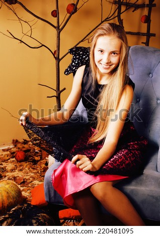 blond cute girl in halloween interior with pumpkin, cute teen smiling celebrating - stock photo