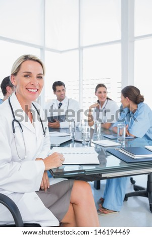 Blond doctor sitting next to her medical team in a bright office - stock photo
