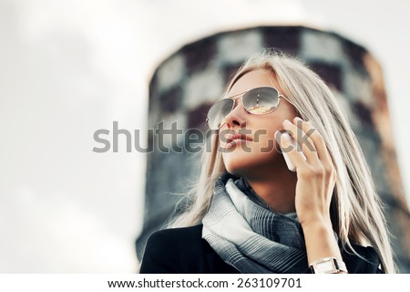 Blond fashion business woman calling on the cell phone outdoor - stock photo
