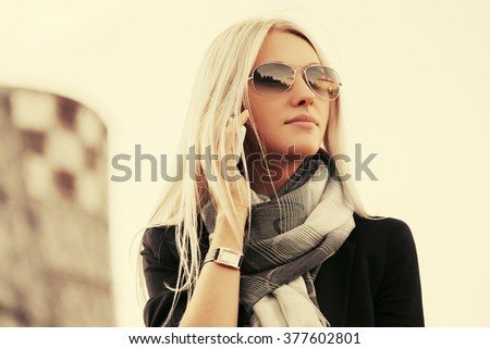 Blond fashion business woman in sunglasses calling on cell phone outdoor - stock photo